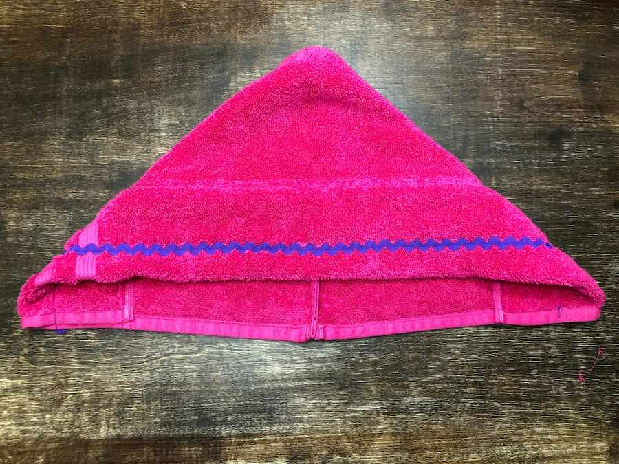 Refold the hand towel into the triangle shape