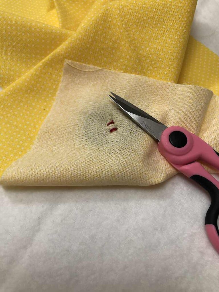 Carefully snip your thread close to the knot for 4-hole button