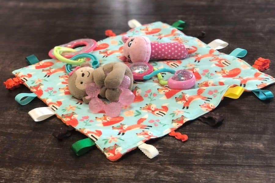 baby toys on top of baby tag blanket