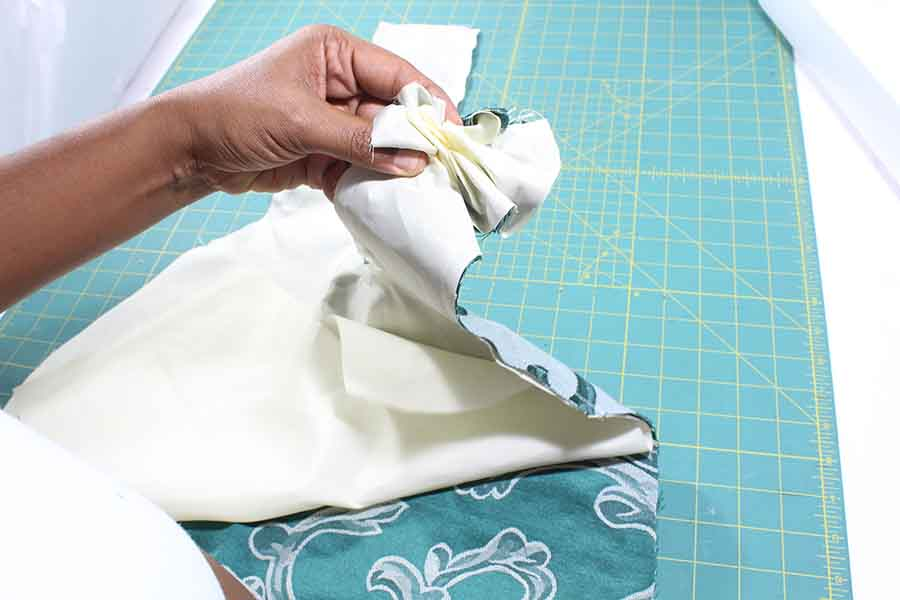 Feed the safety pin inside the handle until appears between the main and lining fabric