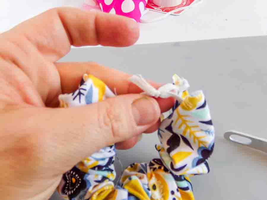 tie the elastic for your no-sew scrunchie in a knot and remove safety pin