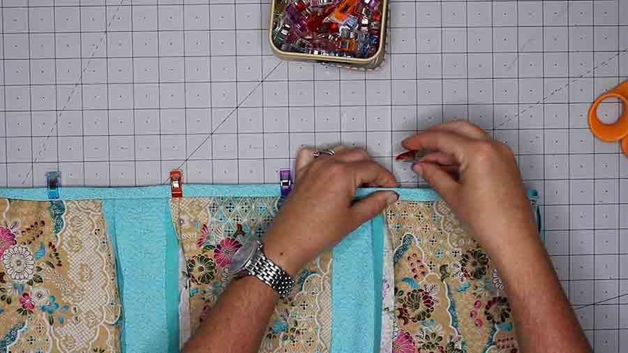 fold raw edge of bias tape toward raw edge of baby rag quilt and fold